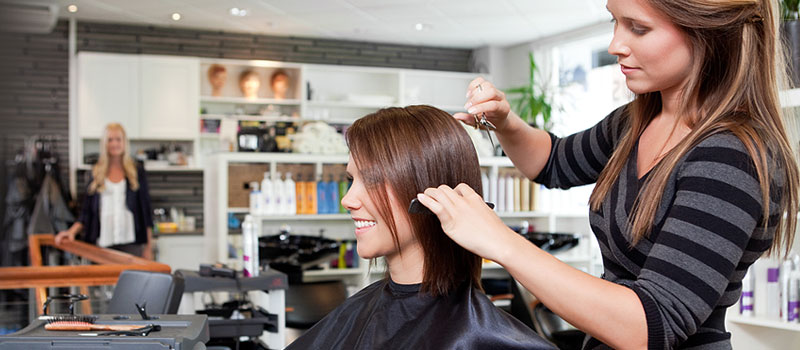 Hair stylist cutting customers hair at UK beauty salon.