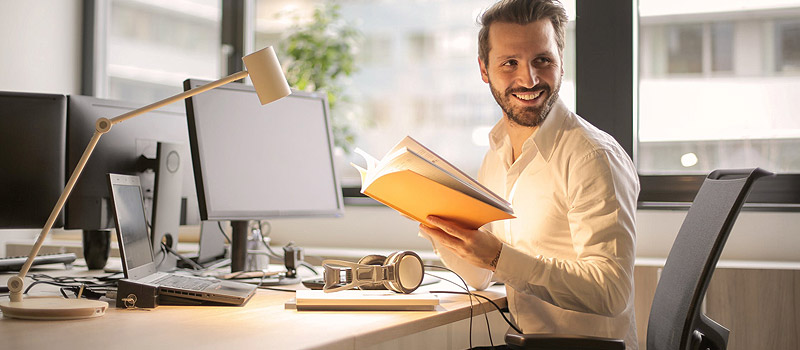 Businessman sitting at his desk at the office with a list of assets his business owns