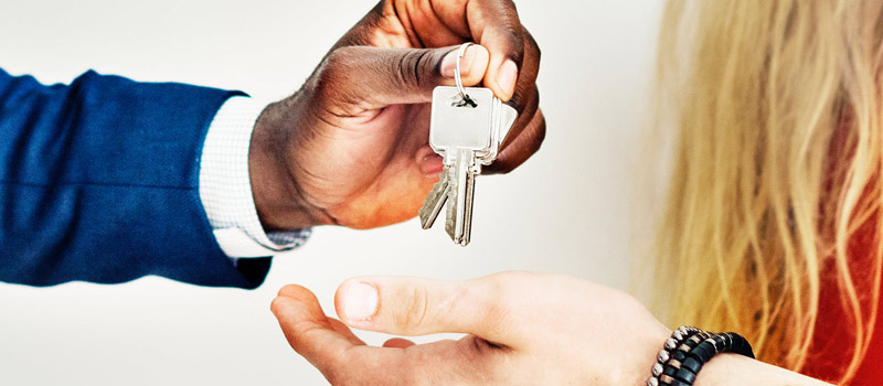 Landlord handing over keys to new tenants