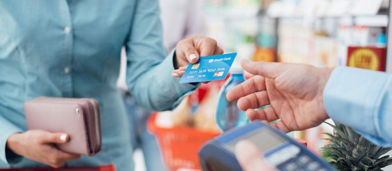 Customer purchasing items by card at a convenience store.